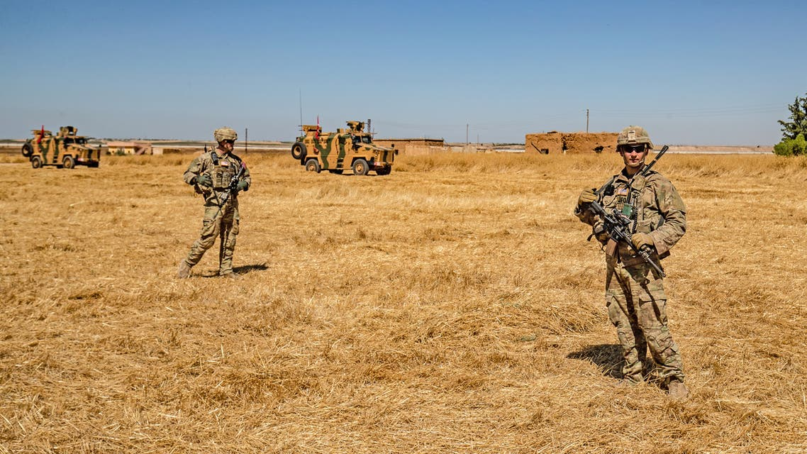 US soldiers stand close to Turkish military vehicles during a joint patrol with Turkey in the Syrian village of al-Hashisha on the outskirts of Tal Abyad town along the border with Turkey  September  2019 REUTERS