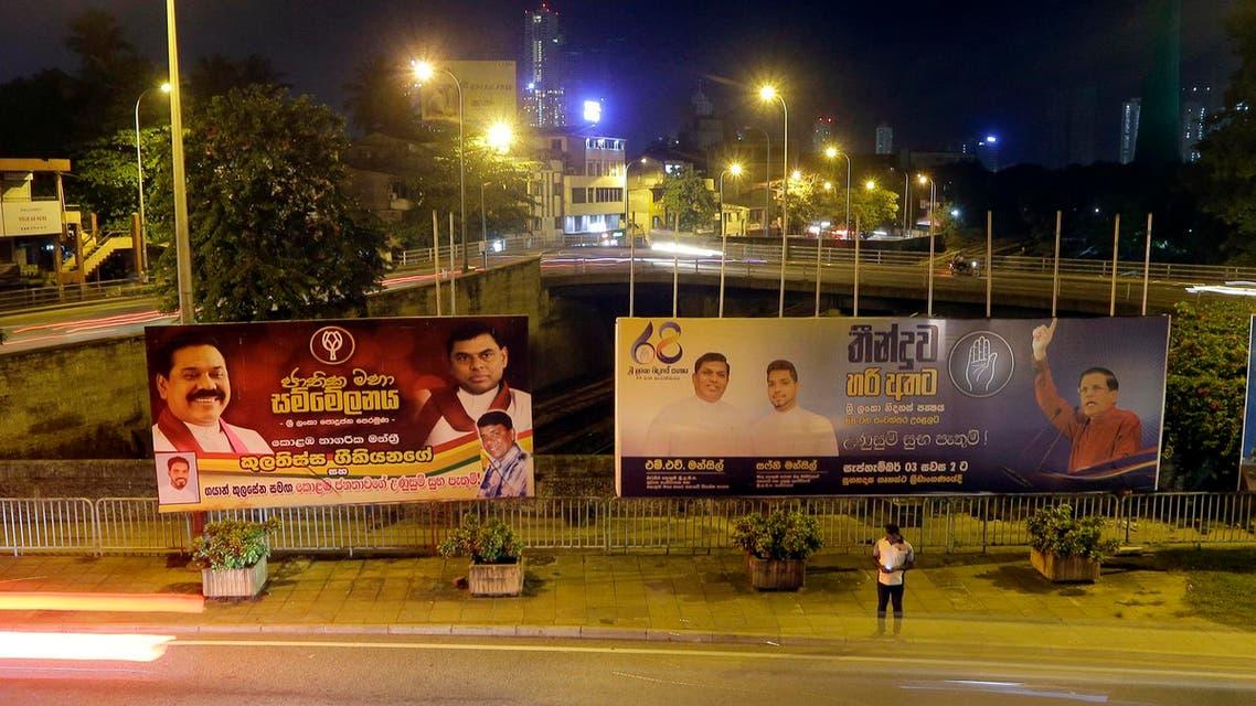 A Sri Lankan man stands near billboards displaying President Maithripala Sirisena, right, and former president Mahinda Rajapaksa, left, in Colombo, Sri Lanka, Wednesday, Sept. 18, 2019. (AP)