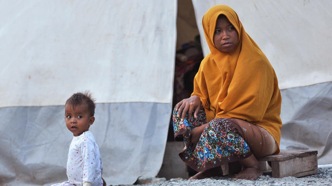 This picture taken on September 25, 2019 shows Ela (R) and her daughter Al (L) sitting in front of their tent at a temporary shelter, in Palu, Central Sulawesi, a year after the magnitude 7.5 quake and subsequent deluge razed swathes of the coastal city killing more than 4,300 people and displacing some 170,000 residents. (AFP)
