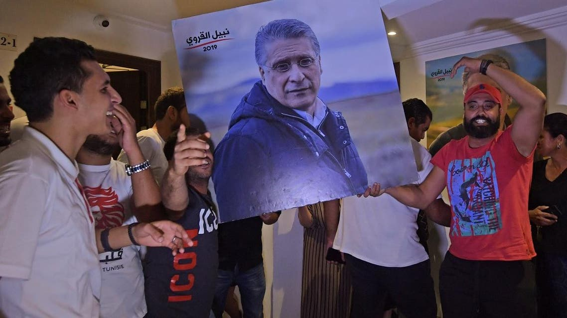 Supporters of Qalb Tounes (Heart of Tunisia) party of jailed business tycoon Nabil Karoui (portrait) cheer in reaction to the first exit polls at the party's office in Tunis on October 6, 2019. (AFP)