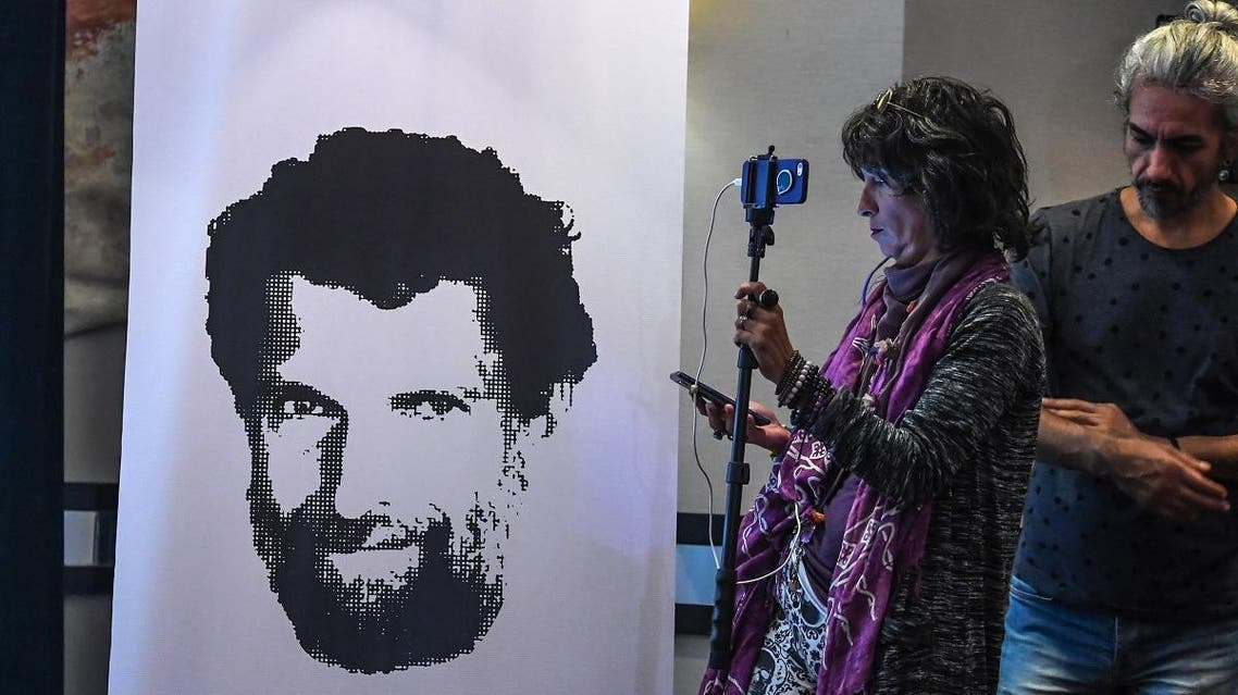 A journalist stands in front of a poster featuring jailed businessman and philanthropist Osman Kavala during a press conference of his lawyers on October 31, 2018. (AFP)