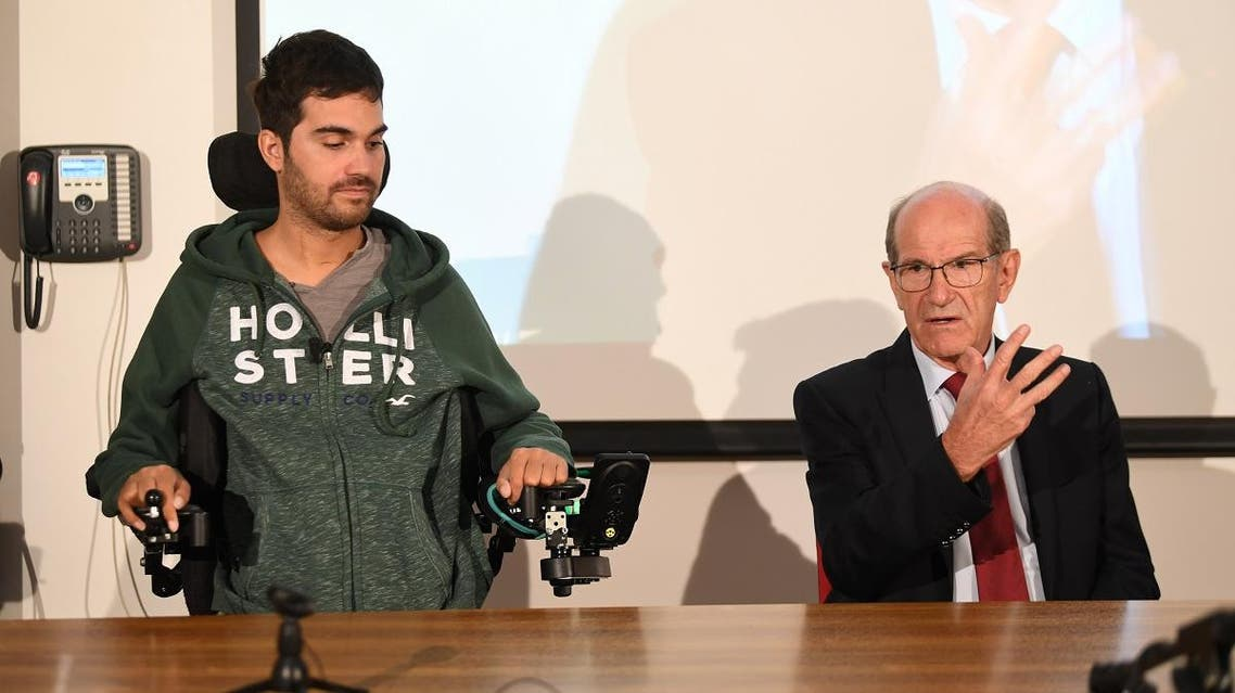 French doctor Alim Louis Benabid (R) and patient Thibault attend a press conference to present the brain-controlled exoskeleton in Grenoble on October 7, 2019. (AFP)