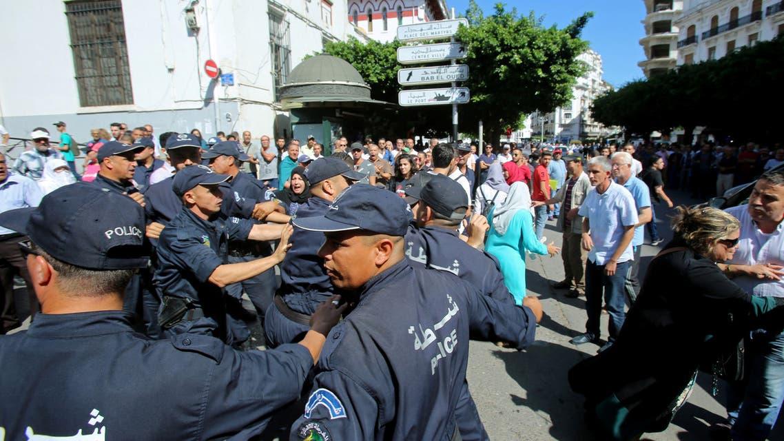 عناصر من الشرطة الجزائرية يحاولون تفريق متظاهرين (8 أكتوبر - رويترز)