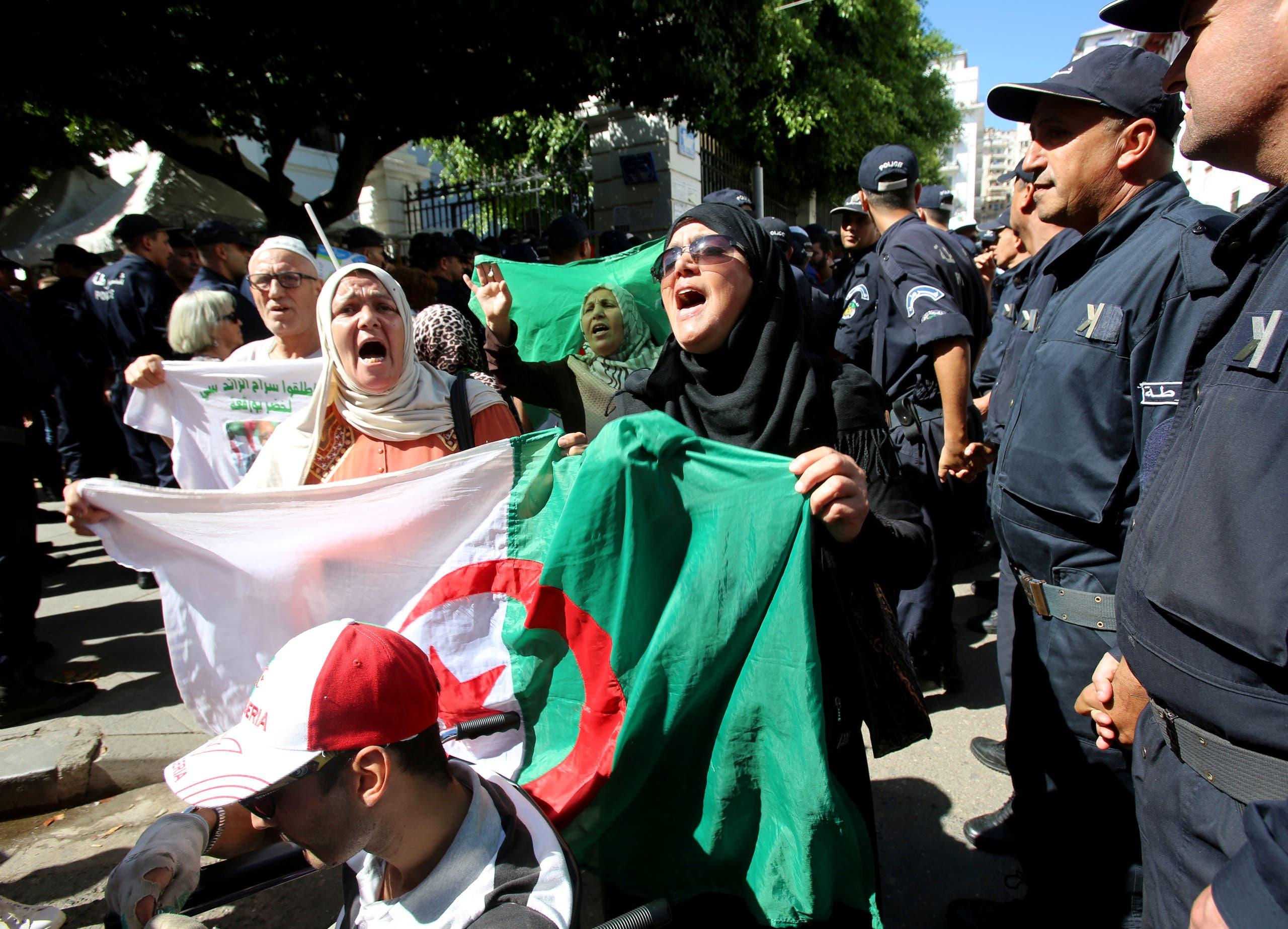عناصر من الشرطة الجزائرية إلى جانب متظاهرين (8 أكتوبر - رويترز)