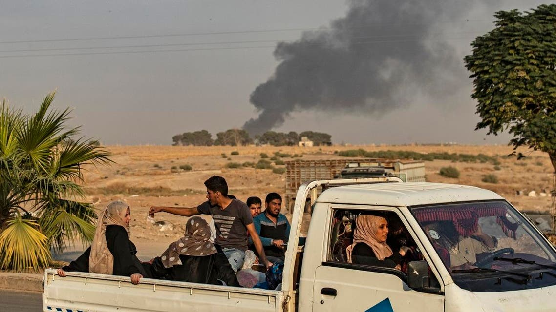 Civilians ride a pickup truck as smoke billows following Turkish bombardment on Syria's northeastern town of Ras al-Ain in the Hasakeh province along the Turkish border on October 9, 2019. (AFP)