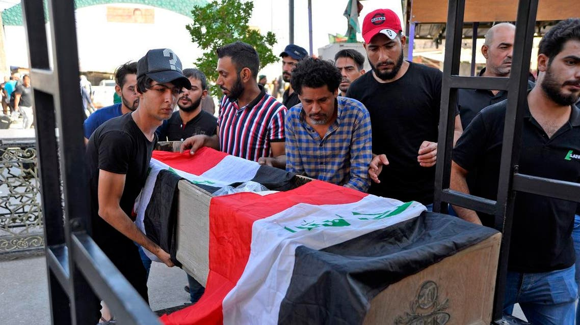 Mourners carry the Iraqi flag-draped coffin of a protester, who was killed amidst clashes in a demonstration, during his funeral in the central Iraqi city of Najaf on October 4, 2019. (AFP)