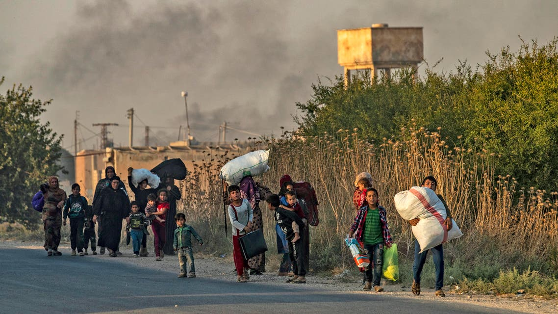 Civilians flee with their belongings amid Turkish bombardment on Syria's northeastern town of Ras al-Ain in the Hasakeh province along the Turkish border on October 9, 2019. (AFP)