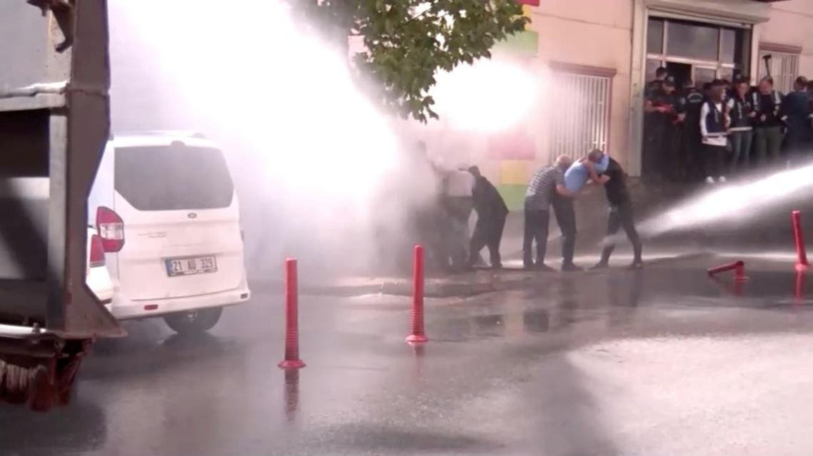 Kurds protesting Turkey's Syria operation are hit by water sprayed from a water cannon in Diyarbakir. (Reuters)