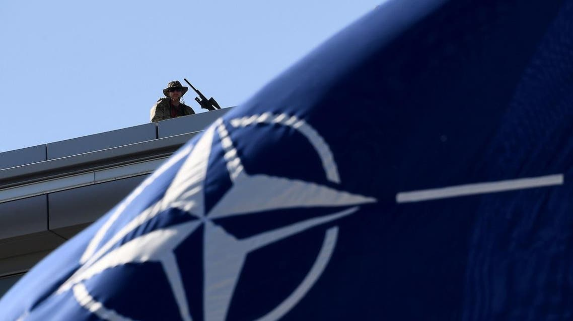 A military personnel stands guard on top of the roof during the NATO (North Atlantic Treaty Organization) summit ceremony at the NATO headquarters, in Brussels. (AFP)