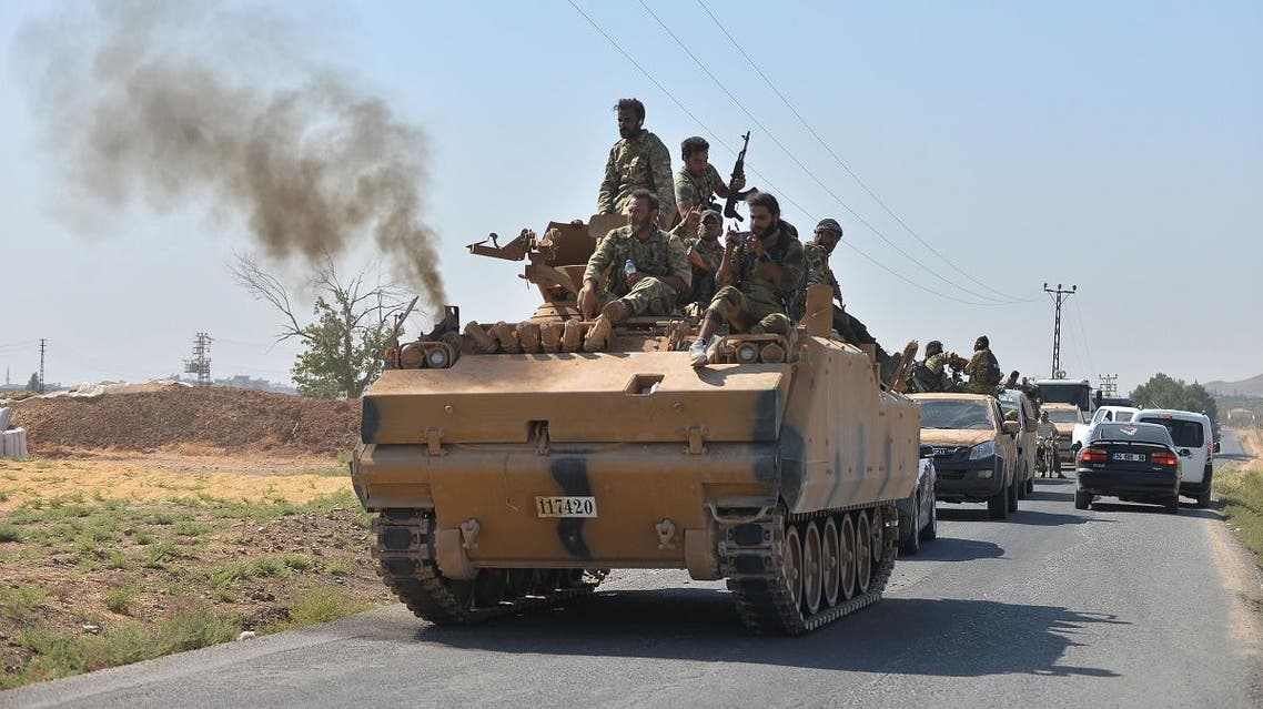 Members of Syrian National Army, known as Free Syrian Army, wave as they drive to cross into Syria near the Turkish border town of Ceylanpinar. (Reuters)