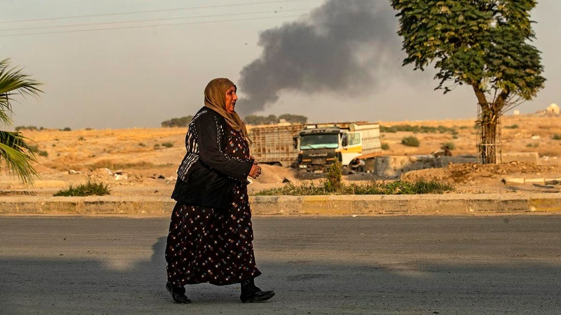 A Syrian woman walks past smoke as Arab and Kurdish civilians flee following Turkish bombardment on Syria's northeastern town of Ras al-Ain in the Hasakeh province. (AFP)