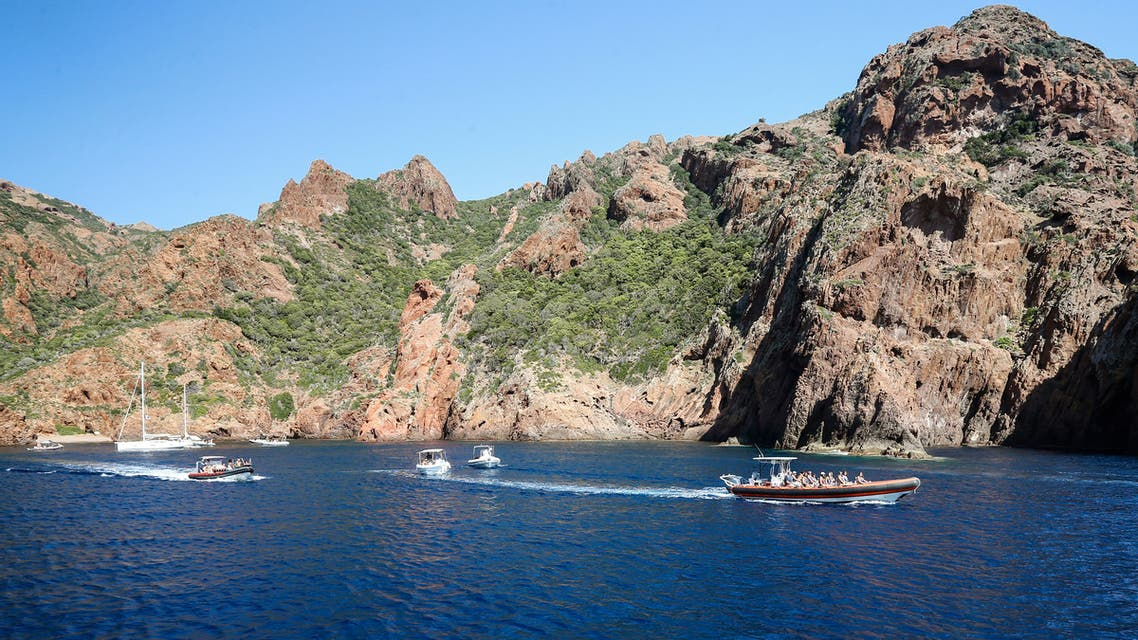 Tourists take a cruise on August 19, 2019, in the Scandola Nature Reserve, on the western coast of the French Mediterranean island of Corsica. The Scandola Nature Reserve park, created in 1975, is an ecological dream, being a nature reserve and a protected marine zone that is listed by France's coastal protection agency and Natura 2000, in addition to its recognition by UNESCO. It is a prime destination for the some three million people who visit Corsica each year, 75 percent of them in the summer. The paradox is that growing numbers of tourists are drawn to Scandola's pristine waters and stunning geological vistas, endangering its fragile ecosystem.