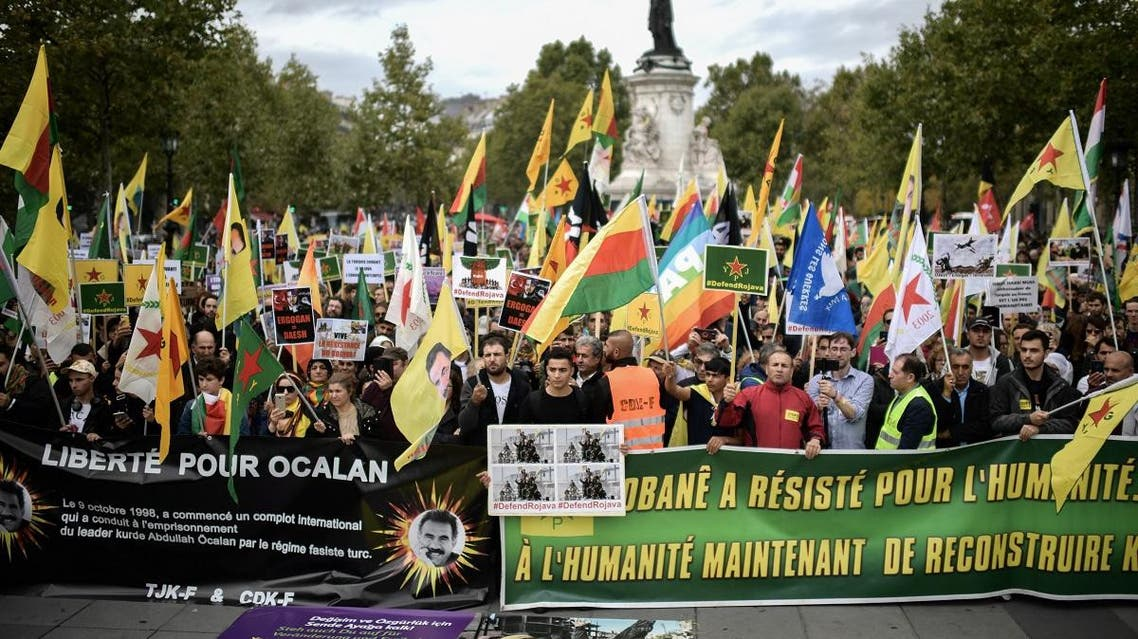 People hold pro-Kurd flags and banner in Paris on October 12, 2019 during a demonstration to support Kurdish militants and protest as Turkey kept up its assault on Kurdish-held border towns in northeastern Syria. (AFP)