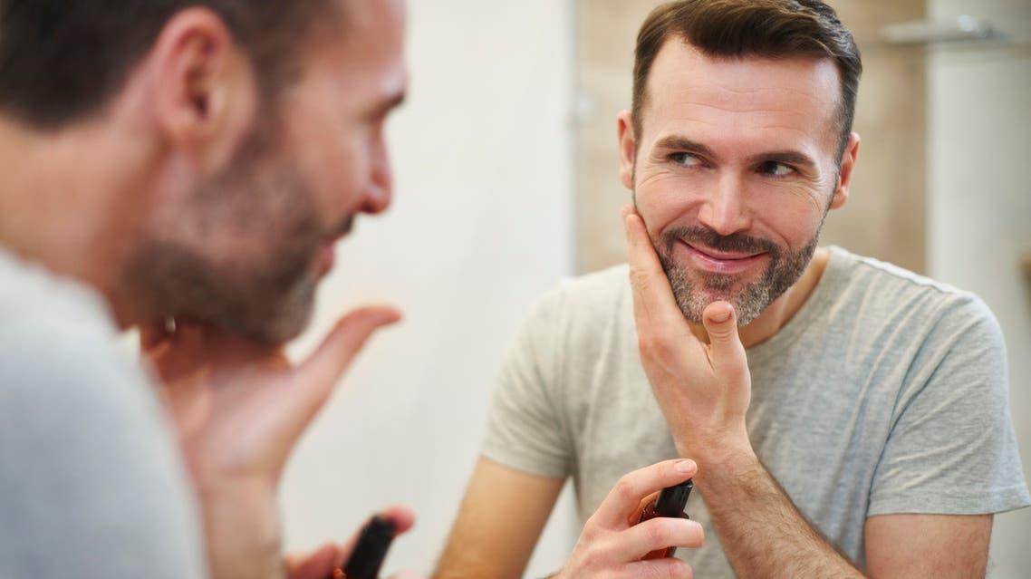 Smiling man applying beauty product on his face stock photo