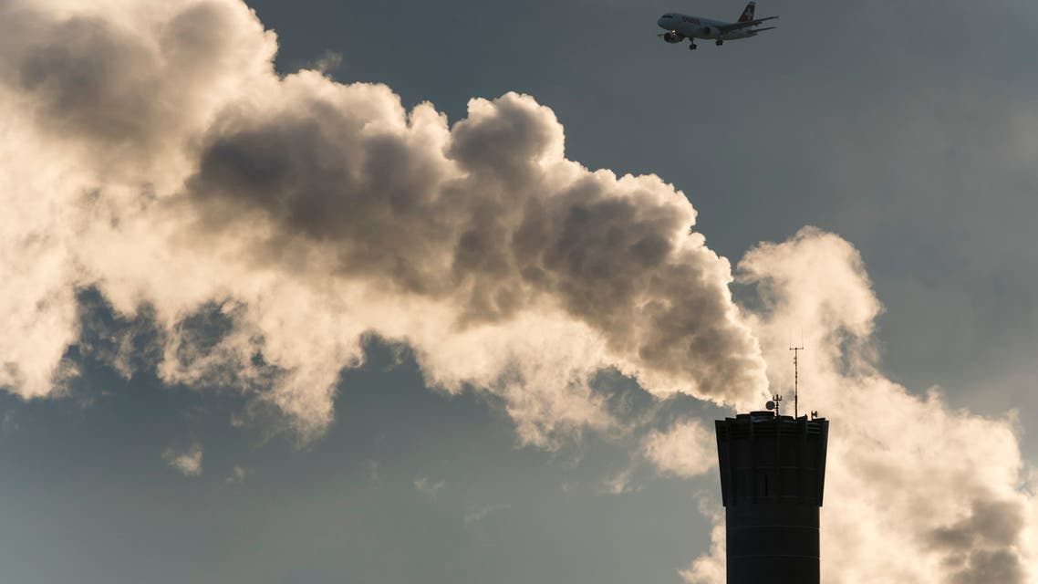 Approaching commercial airplane passes smoking factoty smoke stack stock photo