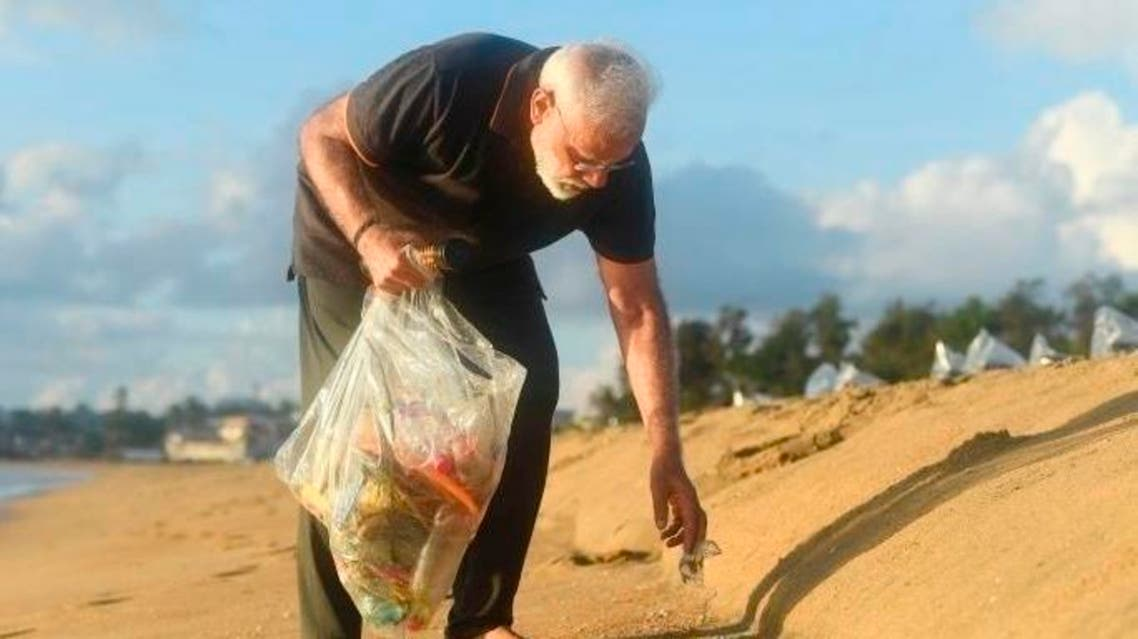 In this handout photo provided by the Indian Prime Minister's Office, Prime Minister Narendra Modi picks trash from a beach in Mamallapuram, India. (AP)