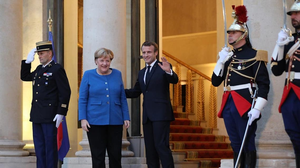 French President Emmanuel Macron (3rdL) and German Chancellor Angela Merkel (2ndL) pose upon her arrival at the Elysee Palace for a working dinner ahead of the EU summit in Paris on October 13, 2019. (AFP)