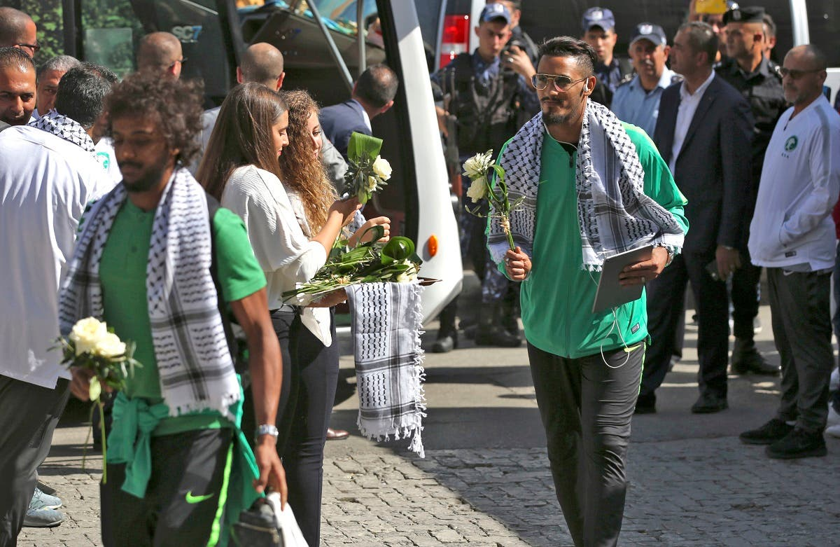 Palestinian women welcome Saudi Arabia's national football players with flowers in Ramallah on October 13, 2019 upon the team's arrival in the occupied Palestinian territories where they will play for the first time next week their match in the Asian qualifiers for the 2022 World Cup against Palestine. (AFP)