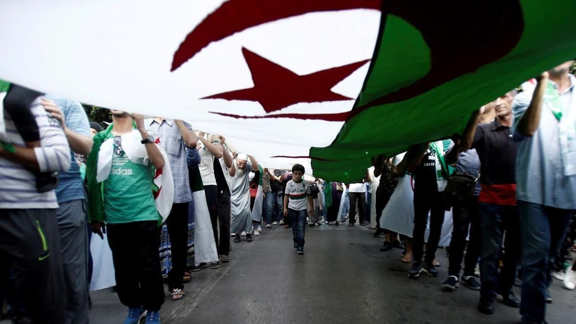 Demonstrators carry a national flag during a protest against the country's ruling elite and rejecting a December presidential election in Algiers, Algeria October 11, 2019. (Reuters)