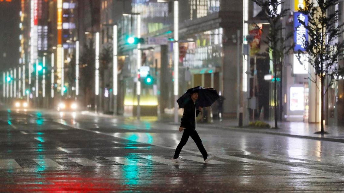 A man walks a pedestrian crossing at Ginza shopping district in the pouring rain due to Typhoon Hagibis in Tokyo. (AP)