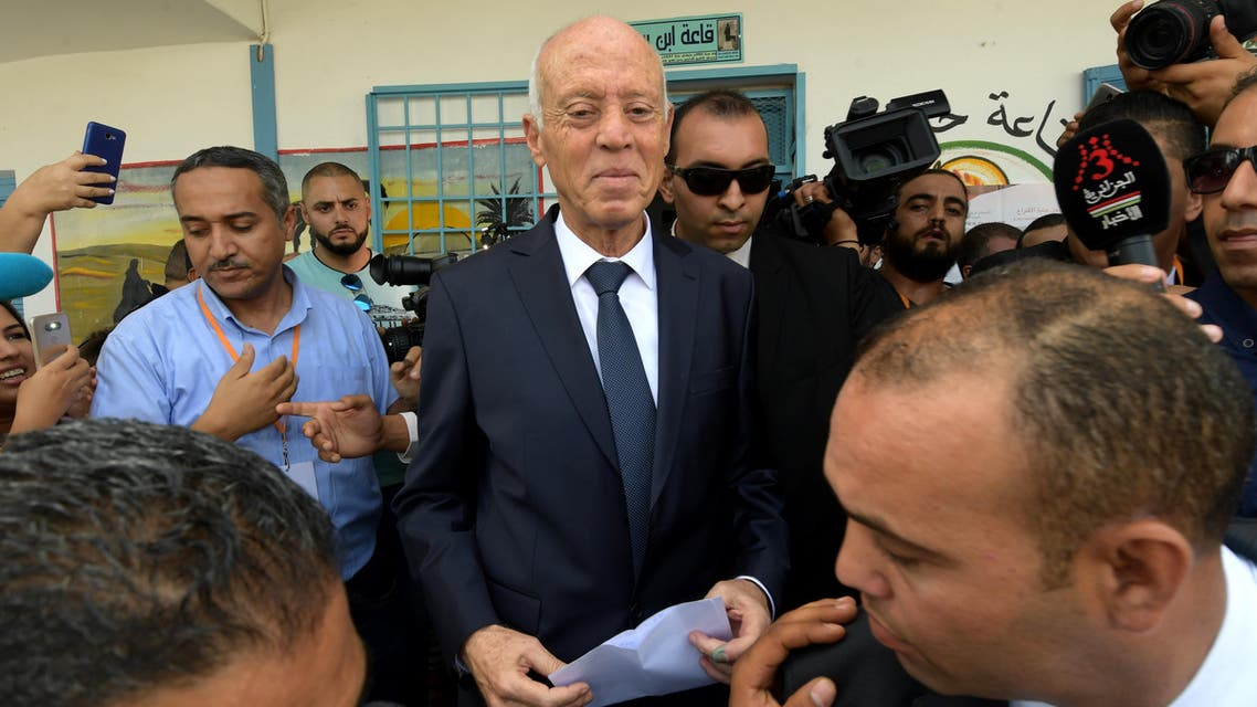 Tunisia's presidential candidate Kais Saied leaves a polling station after casting his ballot in the capital Tunis on October 13, 2019, during the second round of the presidential election. (AFP)