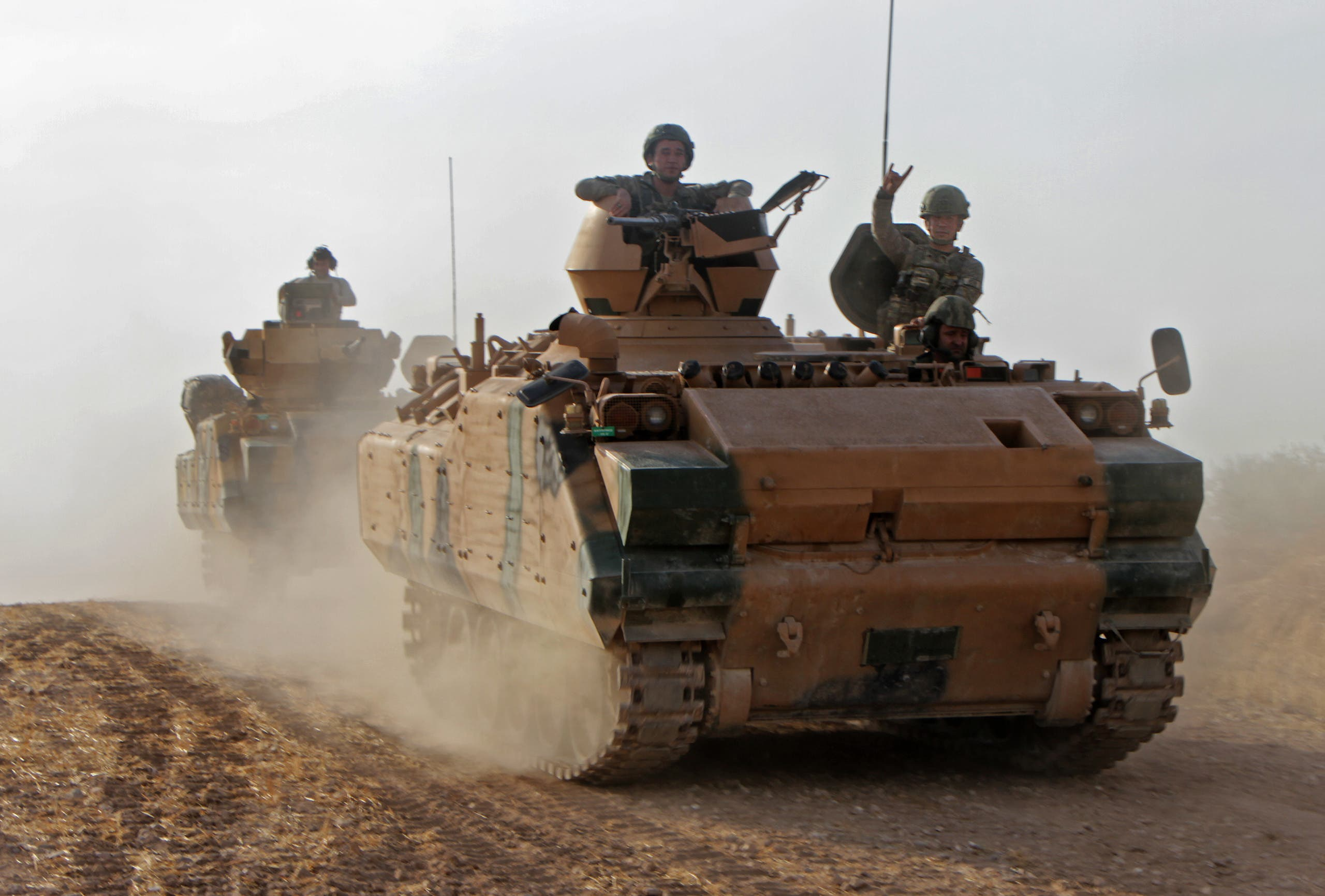 Turkish soldiers are trasported in armored personnel carriers through the town of Tukhar, north of Syria's northern city of Manbij, on October 14, 2019, as Turkey and it's allies continues their assault on Kurdish-held border towns in northeastern Syria. (AFP)