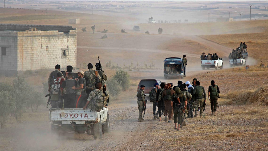 Turkey-backed Syrian fighters are transported in the back of pickup trucks on a road near the village of Qirata on the outskirts of the northern city of Manbij near the Turkish border, on October 14, 2019. (AFP)