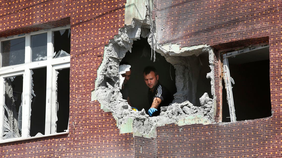A police forensic officer collects evidence from a building damaged by a mortar fired from inside Syra, in Akcakale, Sanliurfa province, southeastern Turkey, Sunday, Oct. 13, 2019. Incoming shells fired from northeastern Syria hit the house earlier on Sunday. Two residents were at the house and were evacuated. (AP Photo/Lefteris Pitarakis)