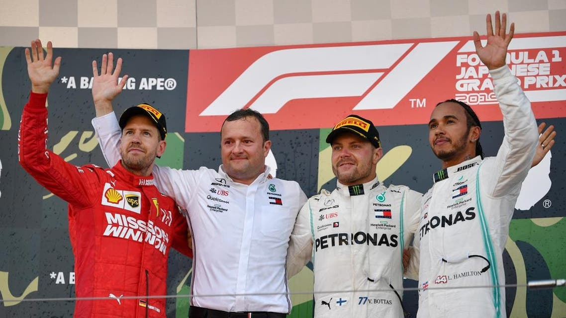 Mercedes' Valtteri Bottas (2nd R) celebrates his victory on the podium with second-placed Ferrari's Sebastian Vettel (L) and third-placed Mercedes' Lewis Hamilton (R) at the end of the Japanese Grand Prix final at Suzuka on October 13, 2019. (AFP)
