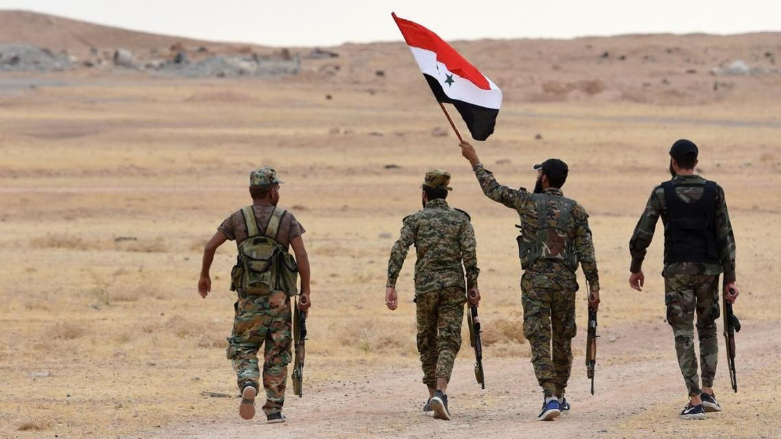 Syrian government forces raise their national flag at Tabqa air base in norther Syria's Raqa region on October 16, 2019. (AFP)