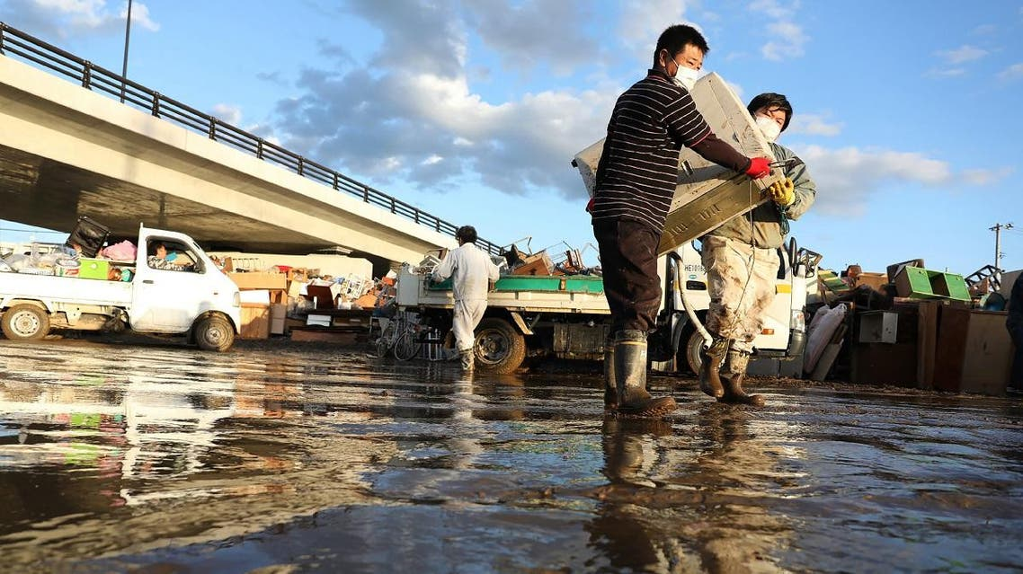 Residents remove muddy items from their flood-damaged homes in Koriyama, Fukushima. (Reuters)