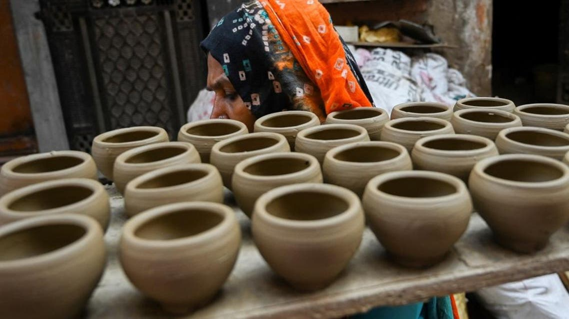 A woman carries earthen pots, at Potter's Village in New Delhi. (AFP)