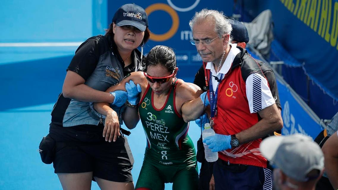 Mexico's Cecilia Perez, center, is helped up by officials after collapsing at the finish line during a women's triathlon test event at Odaiba Marine Park, a venue for marathon swimming and triathlon at the Tokyo 2020 Olympics. (AP)