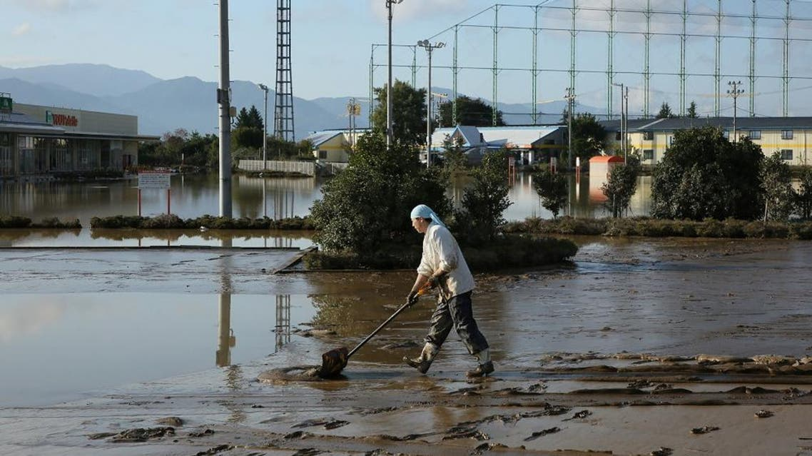 A resident removes mud from an area which was flooded by Typhoon Hagibis in Nagano on October 16, 2019. (AFP)