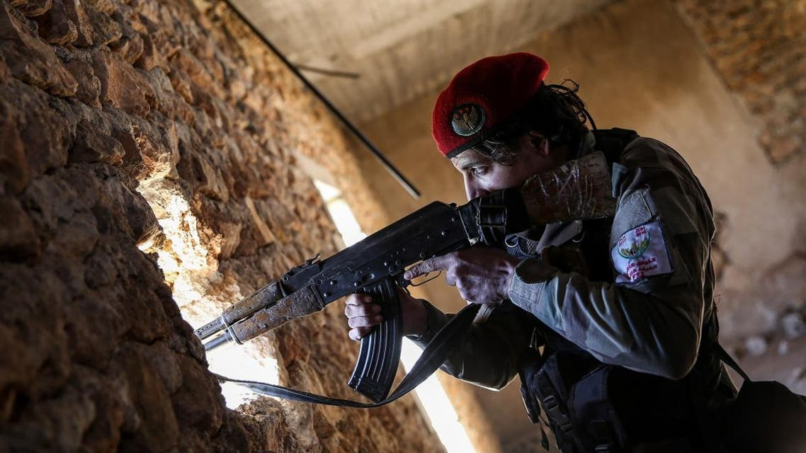 A Syrian fighter of the Turkish-backed Hamza Division aims a Kalashnikov assault rifle from a position in the village of Ulashli near the frontline in the northeast of Aleppo province. (File photo: AFP)