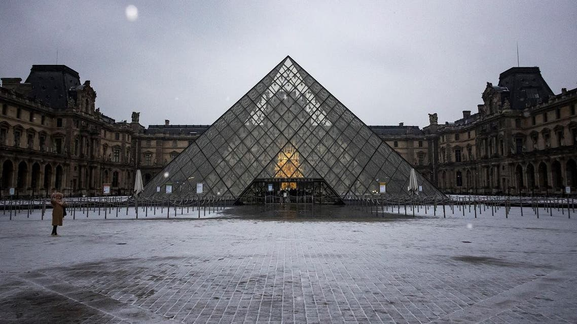 A tourist takes a selfie in front of the Louvre Pyramid in Paris on January 22, 2019. (AFP)