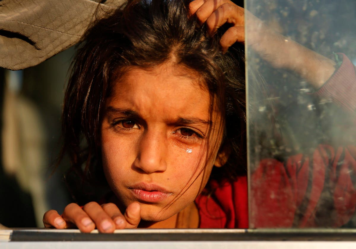 A Syrian girl who is newly displaced by the Turkish military operation in northeastern Syria, weeps as she sits in a bus upon her arrival at the Bardarash camp, north of Mosul, Iraq. (AP)