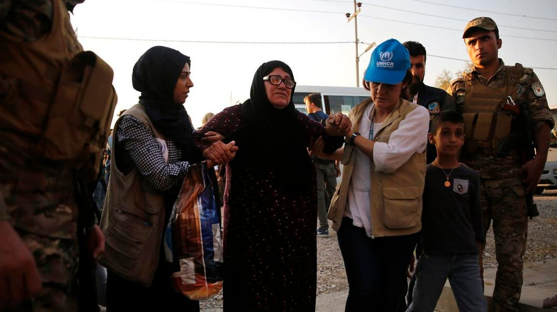 UNHCR members helps a Syrian woman who is newly displaced by the Turkish military operation in northeastern Syria, upon her arrival at the Bardarash camp, north of Mosul, Iraq. (AP)