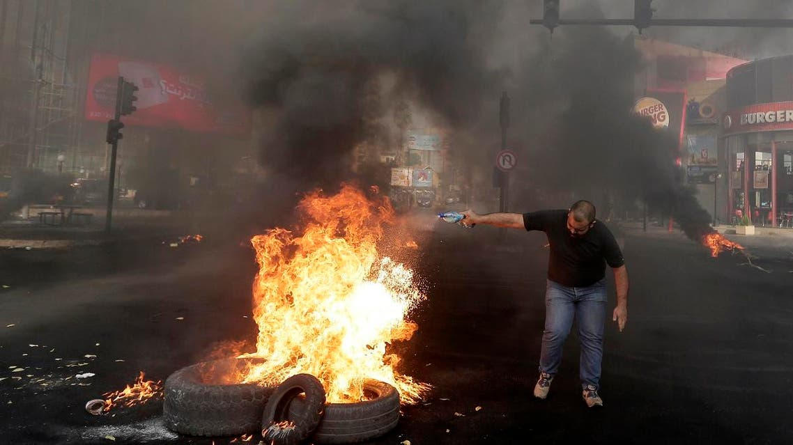 An anti-government protester sets fire on tires to block a road during a protest against government's plans to impose new taxes in Beirut, Lebanon, Friday, Oct. 18, 2019. (AP)