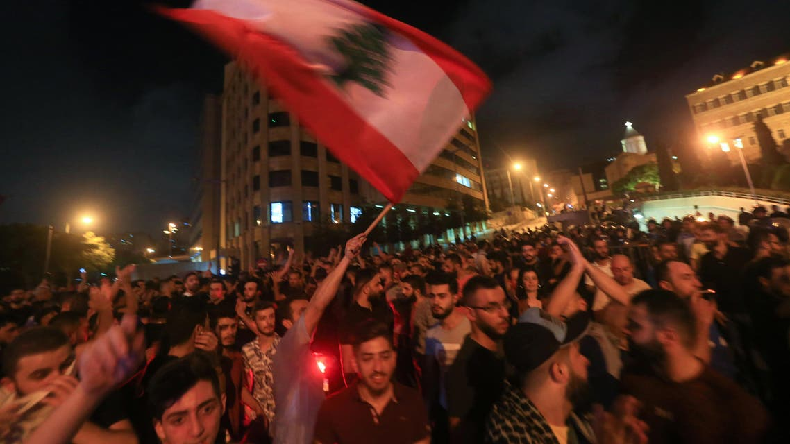 Demonstrators wave a flag during a protest against a government decision to tax calls made on messaging applications on October 17, 2019 outside the government palace in Beirut. (AFP)
