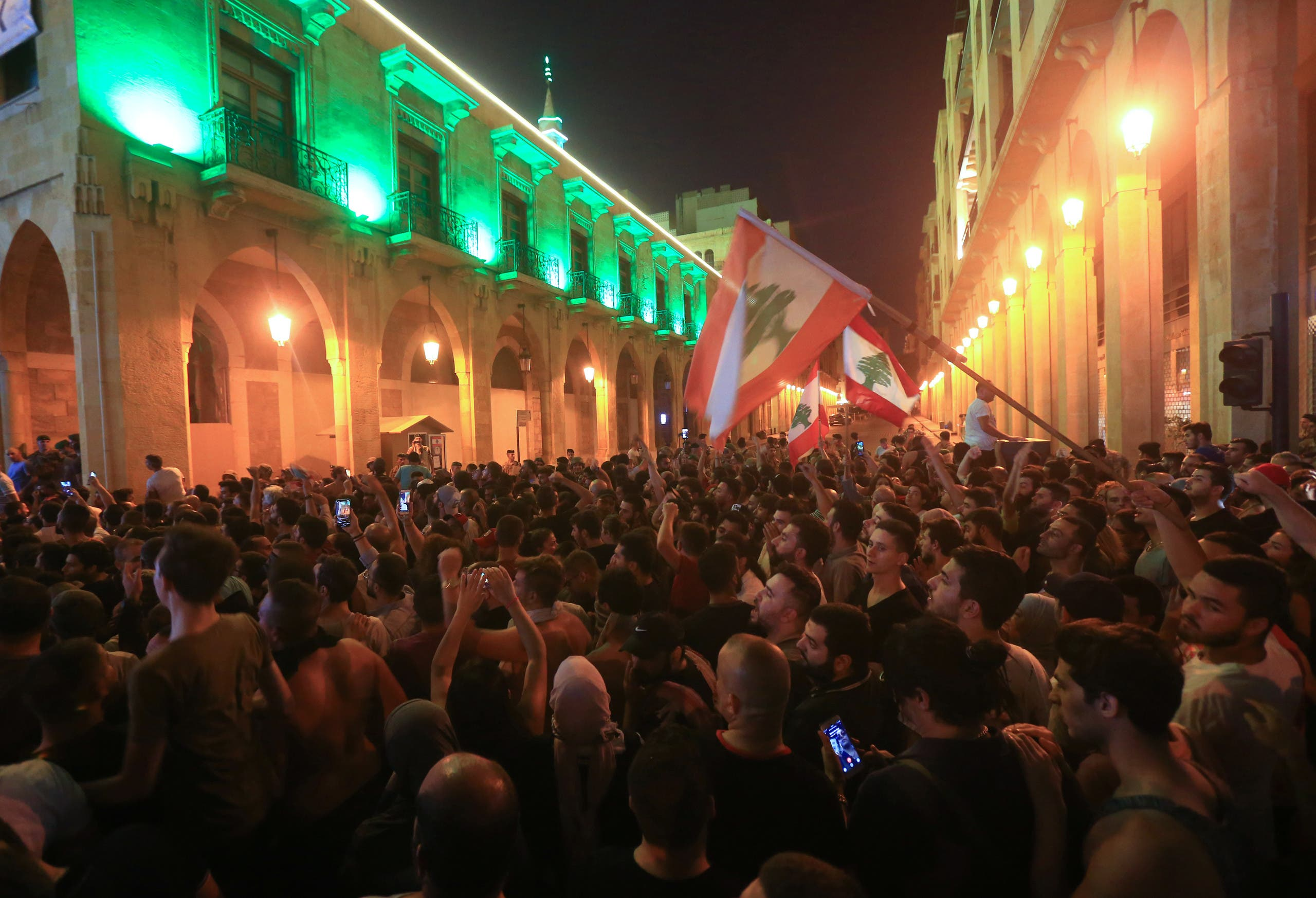 Demonstrators wave flags during a protest against a government decision to tax calls made on messaging applications on October 17, 2019 outside the government palace in Beirut. (AFP)