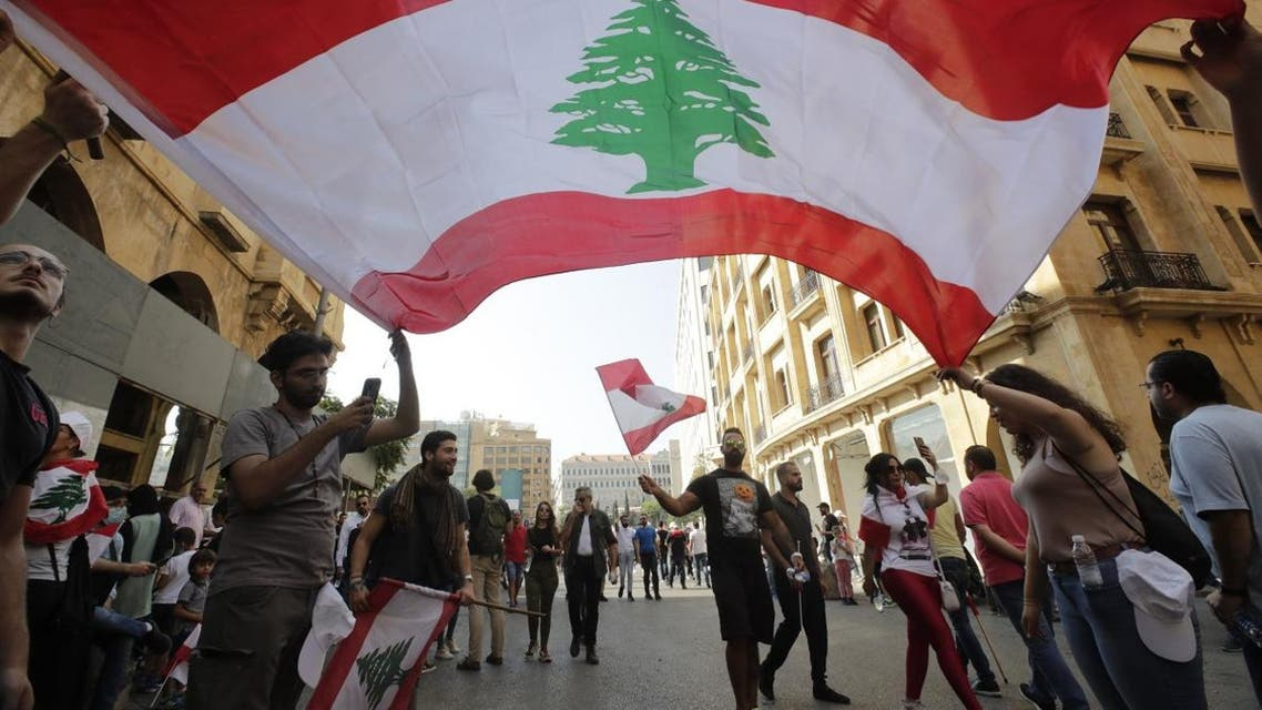 Protesters wave the national flag in downtown beirut as hundreds continued to gather on October 19, 2019 for a third day of protests. (AFP)