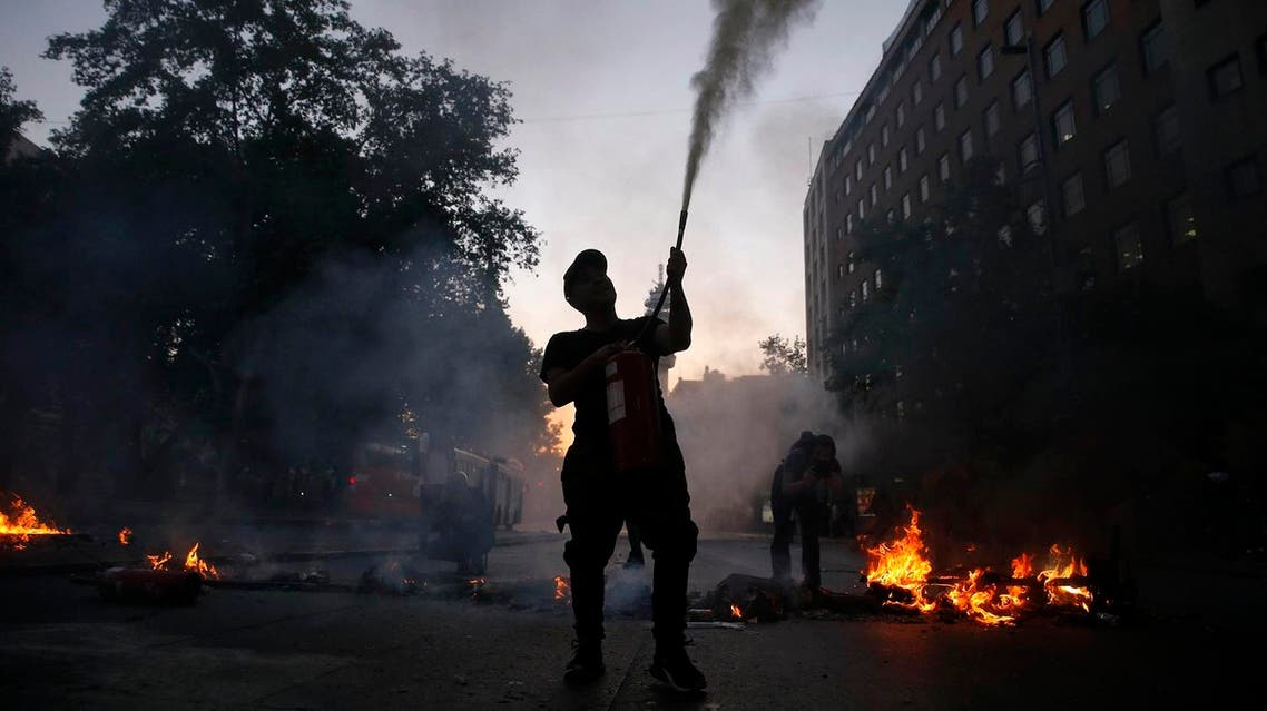 Demonstrators set up barricades following a mass fare-dodging protest in downtown Santiago. afp