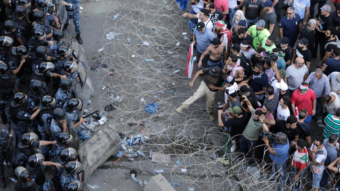 Riot police stand guard as anti-government protesters try to remove a barbed-wire barrier to advance towards the government buildings during a protest in Beirut, Lebanon, Saturday, Oct. 19, 2019. (AP)