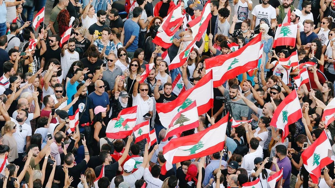 Demonstrators carry national flags and gesture during an anti-government protest in Beirut, Lebanon October 19, 2019. REUTERS