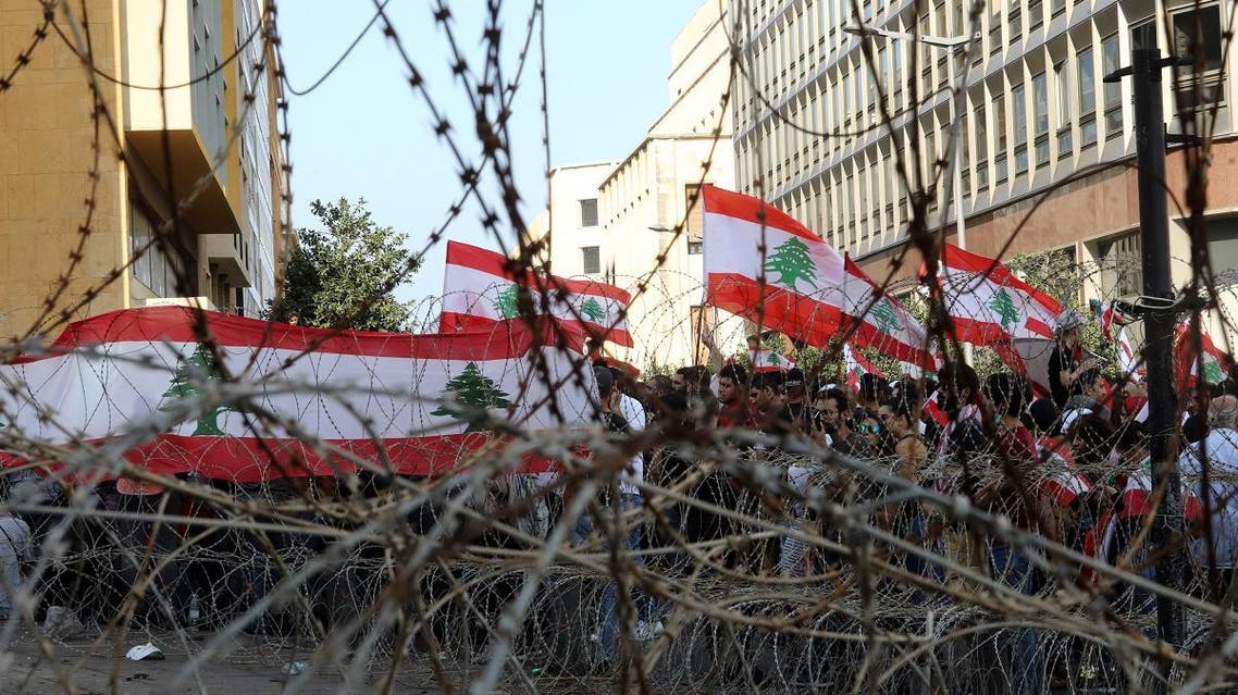 Lebanese demonstrators wave the national flag on barbed wire protecting the government headquarters, known as the Grand Serail in central Beirut, as hundreds continued to gather in Lebanon on October 19, 2019 for a third day of protests. (AFP)