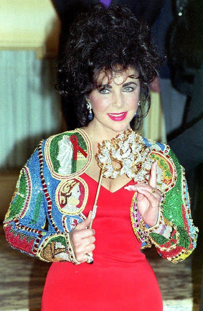 In this file photo taken on April 13, 1992 US actress Elizabeth Taylor holds up a diamond mask for photographers at a fine jewelry auction to benefit the American Foundation for AIDS Research (AmFAR). (AFP)