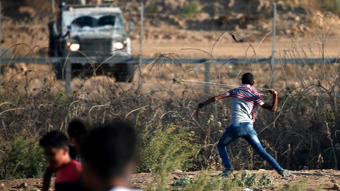 A Palestinian protester uses a slingshot to throw a stone at Israeli forces amidst clashes during a demonstration along the border with Israel east of Bureij in the central Gaza Strip on October 18, 2019. (AFP)
