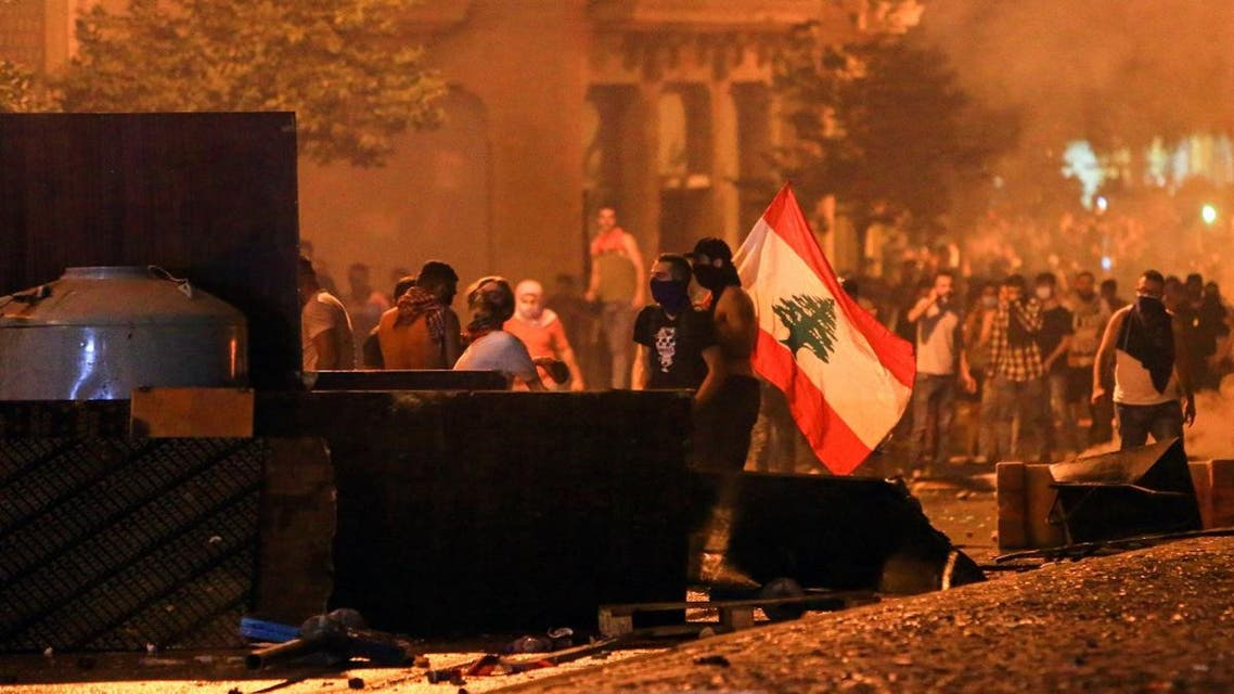 Lebanese demonstrators stand with a national flag behind a make-shift barricade amidst clashes with security forces during a mass protest at Riad al-Solh Square in the centre of the capital Beirut on October 18, 2019 against dire economic conditions. (AFP)
