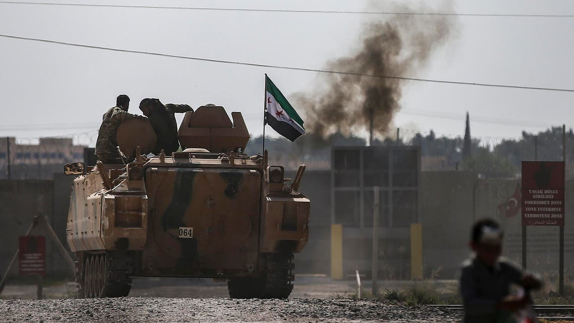 Turkish-backed Syrian opposition fighters on an armoured personnel carrier drive to cross the border into Syria, in Akcakale, Sanliurfa province, southeastern Turkey, Friday, Oct. 18, 2019. (AP)
